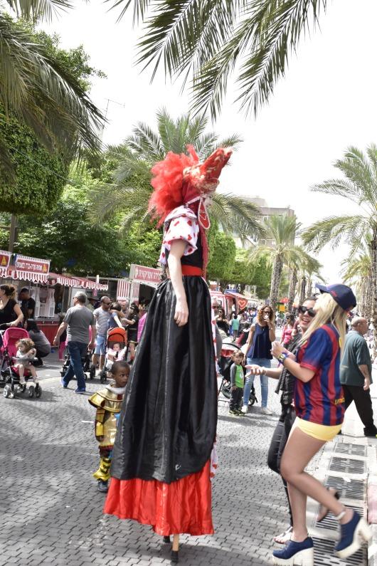 ליצנית על קביים עוברת לידנו A female clown on stilts passes near us
