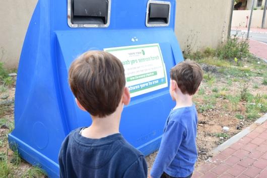 ליד מיכל למיחזור נייר Next to a paper recycling bin