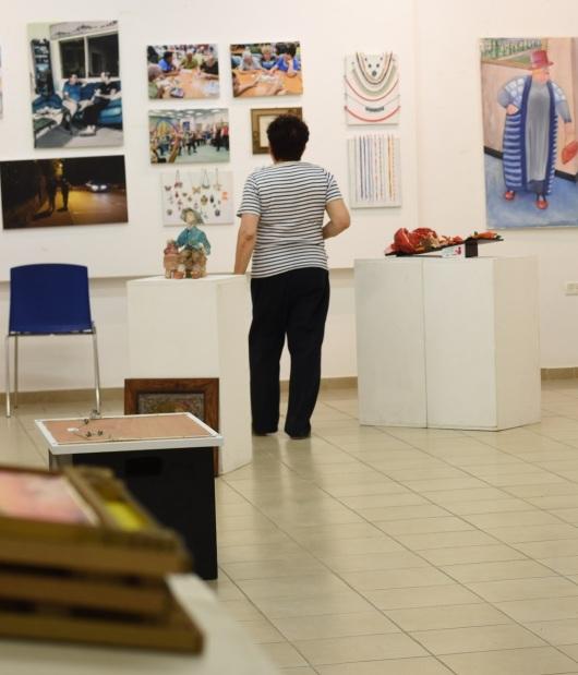 האוצרת בוחנת את היצירות   The curator examines the works